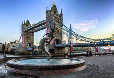 在塔桥梁前面的美人鱼喷泉,在日落 免版税库存照片