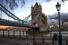 在塔桥梁前面的长凳在日落 图库摄影