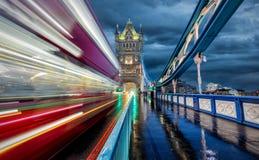 在塔桥梁的移动的红色公共汽车在伦敦 免版税库存照片