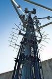 在塔的高帆柱金属结构电信与蓝天 免版税库存照片