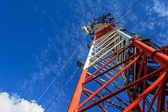 在塔的高帆柱金属结构电信与蓝色s 免版税库存照片