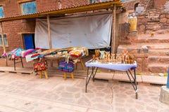 在塔附近的纪念品市场在Sillustani,秘鲁,南美。有五颜六色的毯子的,围巾,布料,雨披街道商店 库存图片