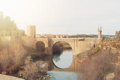 在塔霍河和它的反射的曲拱阿尔坎塔拉桥梁 库存图片