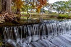 在塞浦路斯树附近的美丽的梦想的流动的帷幕瀑布在得克萨斯小山国家。 免版税库存图片