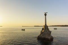 在塞瓦斯托波尔海湾的日落 纪念碑被破坏的船 库存照片