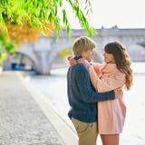 在塞纳河堤防的年轻约会夫妇 免版税库存照片