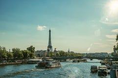 在塞纳河,桥梁和艾菲尔铁塔的小船日落的在巴黎 免版税库存照片
