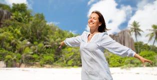 在塞舌尔海岛热带海滩的愉快的妇女 免版税库存图片
