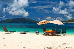 在塞舌尔群岛的热带海滩有野餐桌的 免版税库存图片