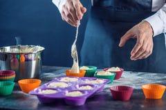在填装面团的一条黑围裙的厨师酥皮点心入杯形蛋糕硅树脂模子 糖果店烹调的概念 库存图片