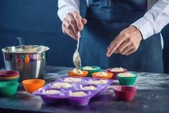 在填装面团的一条黑围裙的厨师酥皮点心入杯形蛋糕硅树脂模子 糖果店烹调的概念 免版税库存照片
