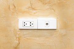 在墙壁、电以太网和天线插口的角落的电源插座 图库摄影