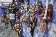在墙壁上垂悬的五颜六色的编织帽子 库存图片