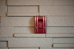 在墙壁上的一个火警拖拉箱 免版税库存照片