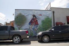 在墙壁上的一张夫妇乘驾自行车街道画 库存图片