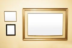 在墙壁上的三个空白的框架 库存照片