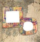 在墙壁上的两个空白的五颜六色的被绘的纸板框架 库存图片