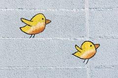 在墙壁上的两只逗人喜爱的矮小的黄色鸟 免版税库存图片