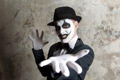 戴在墙壁上的可怕邪恶的小丑一顶圆顶硬礼帽 免版税图库摄影