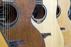 在墙壁上的声学吉他吊连续 软绵绵地集中 图库摄影