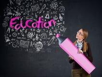 在墙壁上的女小学生文字-教育 免版税图库摄影