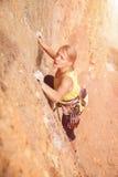 在墙壁上的女性攀岩运动员 免版税图库摄影