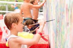 在墙壁上的小男孩油漆 免版税库存图片