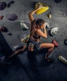 在墙壁上的年轻女人佩带的运动服实践的攀岩户内 库存图片