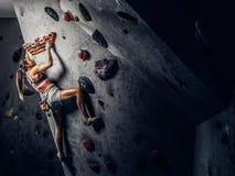 在墙壁上的年轻女人佩带的运动服实践的攀岩户内 图库摄影