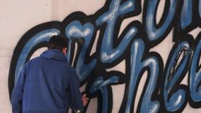 在墙壁上的年轻都市画家图画街道画信件 免版税库存图片