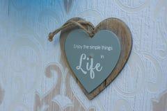 在墙壁上的心形的木制框架标志吊,读在生活中享受简单的事 库存图片