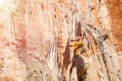 在墙壁上的成熟男性攀岩运动员 免版税图库摄影