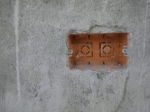 在墙壁上的橙色插口箱子nstallation 免版税库存照片