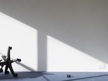 在墙壁上的残破的办公室椅子铸件阴影 免版税图库摄影