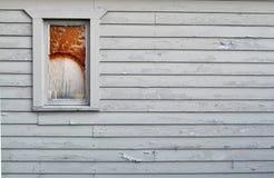 在墙壁上的残破的窗口有削皮油漆的 免版税库存照片
