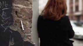 在墙壁上的注射器-考虑人生的被转动的后面的消沉的意思的吸毒者年轻红头发人妇女和 影视素材