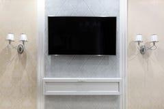 在墙壁上的电视有装饰的和在边的两灯台 库存照片