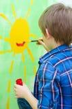 在墙壁上的男孩绘画 图库摄影
