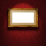 在墙壁上的空的金黄框架。 库存照片