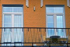在墙壁上的窗口和玻璃门有阳台和家具的 图库摄影