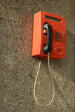 在墙壁上的红色电话 库存图片