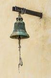 在墙壁上的老古铜色响铃有绳索的 免版税库存照片