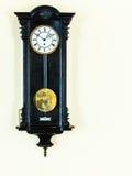 在墙壁上的老摆钟 免版税库存照片