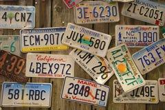 在墙壁上的老汽车许可证板材 库存照片