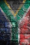 在墙壁上的脏的南非旗子 图库摄影