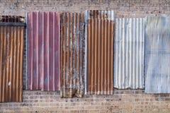 在墙壁上的脏的金属盘区 免版税库存图片