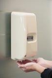 在墙壁上的自动液体皂分配器 免版税库存图片