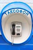 在墙壁上的蓝色投币式公用电话 库存照片
