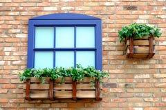 在墙壁上的蓝色窗口由砖做成 免版税库存图片