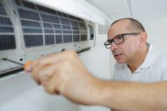 在墙壁上的被聚焦的杂物工测试空调 免版税库存图片